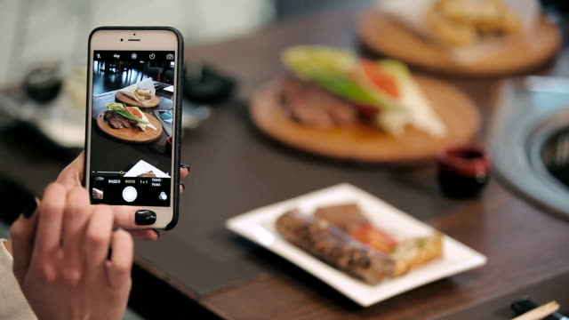 Girl photographing her dinner on a smartphone video