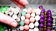 Girl picks in the market and trying beads and pendants. video