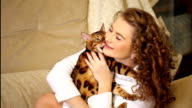 Girl playing and biting Bengal cat. video