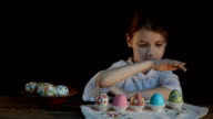 Girl playing Easter eggs in trays. video