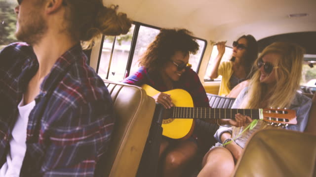 Girl playing guitar on road trip video