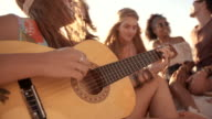 Girl playing her guitar on the beach with friends video