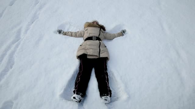 Girl playing in the snow angel video