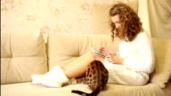 Girl playing on a tablet computer. Bengal cat. Pet. video