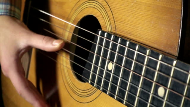 Girl playing on acoustic guitar, slow motion 500 fps video