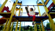 Girl playing on the playground. Laughter, fun, sunshine in her hair. He is sitting and looking at the camera video