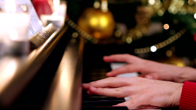 Girl playing piano near Christmas tree video