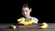 Girl playing with a toy dog made from banana and eats video
