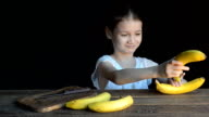 Girl playing with bananas. Black background video