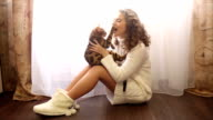 Girl playing with Bengal cat on the floor. video