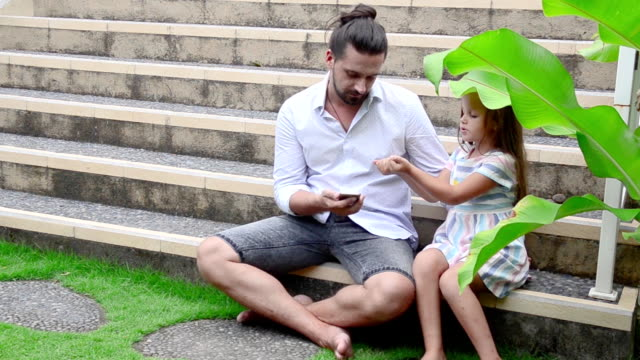 Girl playing with her father. Guesses which hand. video