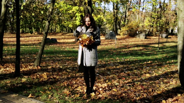 Girl playing with leafs in park in autumn. video