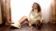 Girl plays with a Bengal cat. Beads. video