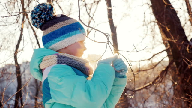 Girl plays with a snow-covered branch of a tree in the rays of the setting sun. Winter joy video