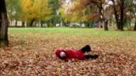 Girl plays with autumn fallen leaves video