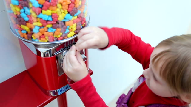 Girl pokes coin in machine sale of sweets video