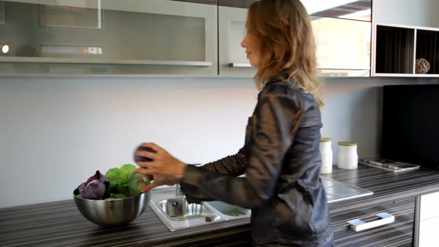 Girl puts fresh vegetables into bowl video