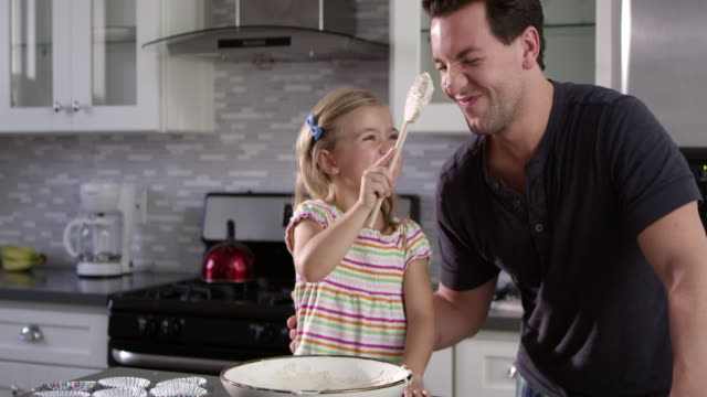 Girl putting cake mix mix on dad's nose while they bake together, shot on R3D video