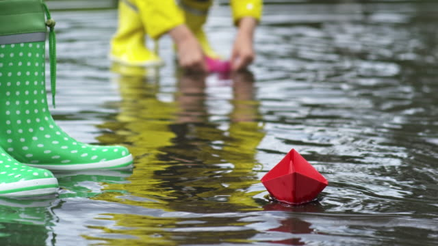 Girl Putting Paper Boat in Puddle video