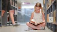 DS Girl reading a book sitting by bookshelf in library video