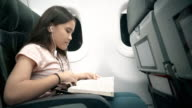 Girl reading book in airplane video