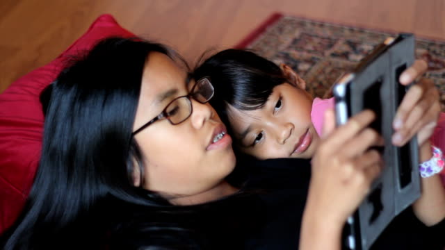Girl Reads Story To Little Sister Off Tablet video