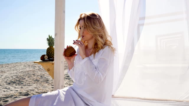 girl resting on beach, drinking coconut juice, Beautiful woman sitting in bungalow with white curtains on shore video