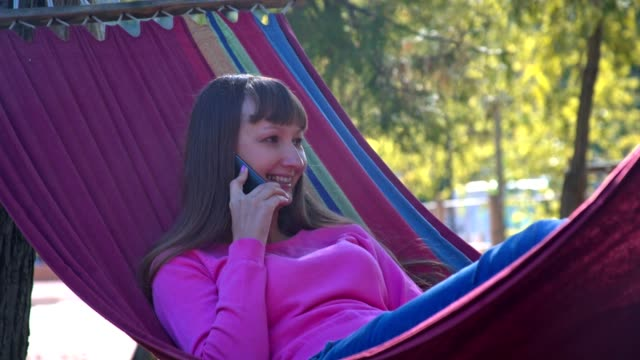 Girl resting on hammock and speaking on her mobile phone video
