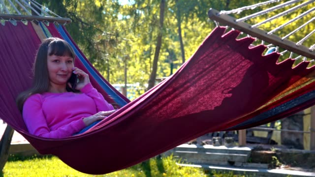 Girl resting on hammock and speaking on the mobile phone video