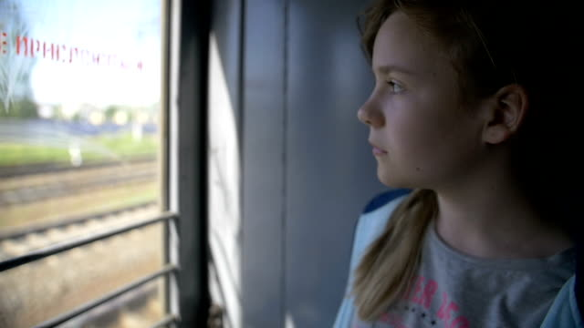 Girl rides on the train looking out the window thinking, slow motion video