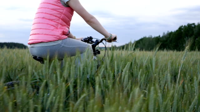 girl riding a bicycle on a wheat field video