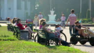 Girl riding bicycle car in park. People having rest on benches. Summer relax video
