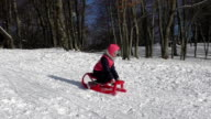 Girl riding on a sled and laughs. video