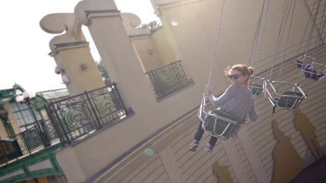 Girl riding the chairoplane in an amusement park video