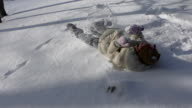 Girl rolling in snow and playing. video