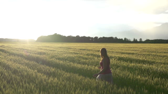 AERIAL SLOW MOTION: Girl running in wheat field video