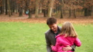 Girl running into father's arms in park video