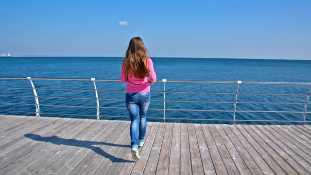 Girl running on a pier video