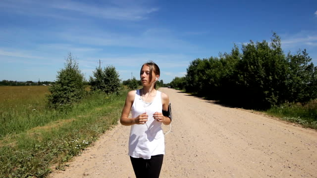 Girl runs on the road in a field video