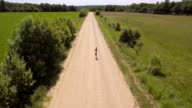Girl runs on the road in a field.Aerial view video