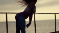 Girl shakes her booty on the pier near the sea at a sunset video
