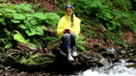 Girl sits by the river and communicates via smartphone video