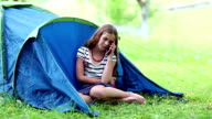 Girl sits on grass near tourist tent and speaks on cell phone video