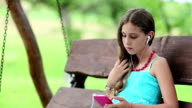 Girl sits on the bench and uses smartphone video
