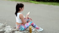 girl sitting and stares at the phone, drinking water video