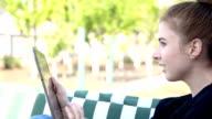 Girl sitting in garden swing using tablet, smiling video