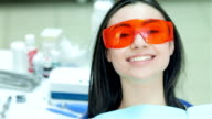 Girl sitting in the dental chair in red protective glasses video