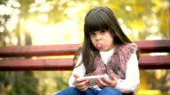 Girl sitting on a bench and using phone video