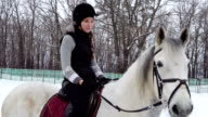 Girl sitting on a horse and resting. At the girl and the horses a break between workouts. Girl smiles. Quiet winter cloudy day. A bit snow falls. video