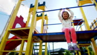 Girl six years old sitting on the playground, laughing. In her hair the sun shines video